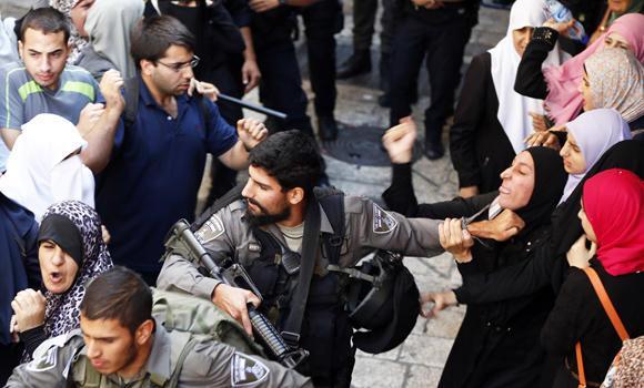 Forze di sicurezza israeliane colluttazione con una donna palestinese dopo che le autorità limitano l'accesso di fedeli musulmani al complesso della moschea di Al-Aqsa nella città vecchia di Gerusalemme la Domenica. (AFP PHOTO / AHMAD GHARABLI)