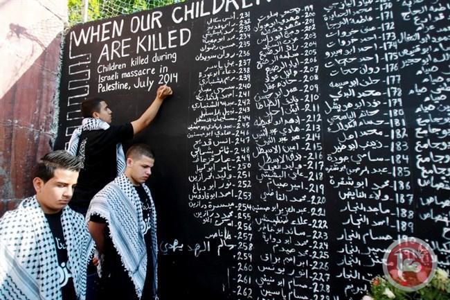 Giovani palestinesi scrivere i nomi dei bambini uccisi durante la guerra della scorsa estate nella Striscia di Gaza. (AFP / Musa Al Shaer, File)