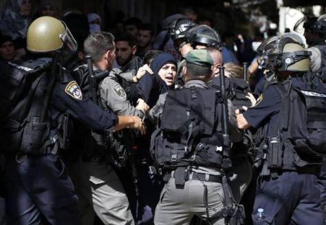 Forze di sicurezza israeliane colluttazione con una donna palestinese dopo che le autorità limitano l'accesso di fedeli musulmani al complesso della moschea di Al-Aqsa