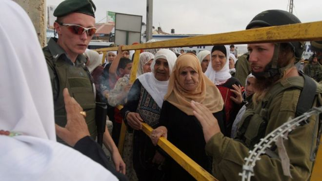 Palestinian women wait to cross the Qalandiya checkpoint outside the West Bank city of Ramallah.Jalaa Marey / JINI