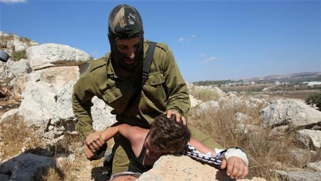 An Israeli soldier beating 12-year-old Mohamed al-Tamimi with a broken arm in the occupied West Bank village of Nabi Saleh near Ramallah on August 28, 2015 (AFP)