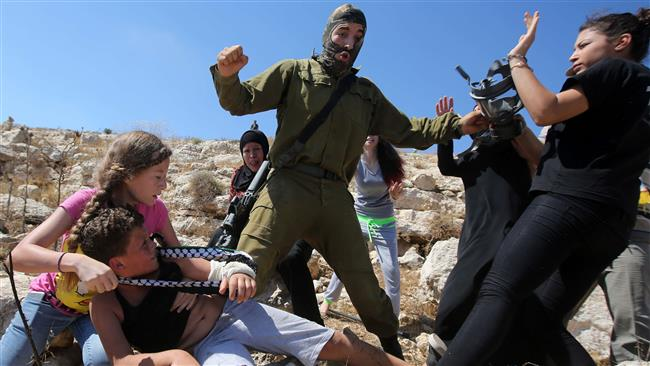 Palestinian women try to prevent an Israeli soldier from arresting 12-year-old Mohamed al-Tamimi with a broken arm during an anti-settlement demo in the occupied West Bank village of Nabi Saleh near Ramallah, August 28, 2015. (AFP)