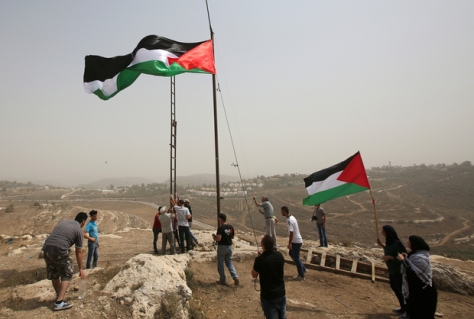 Palestinians celebrate the United Nations General Assembly decision to allow the flag of Palestine -- which has a non-member observer status -- to be hoisted alongside those of member states at the UN headquarters, by raising a large version of their national flag in the occupied West Bank village of Nabi Saleh near Ramallah on September 11, 2015 as they also gather to demonstrate against Jewish settlements. AFP PHOTO / ABBAS MOMANI