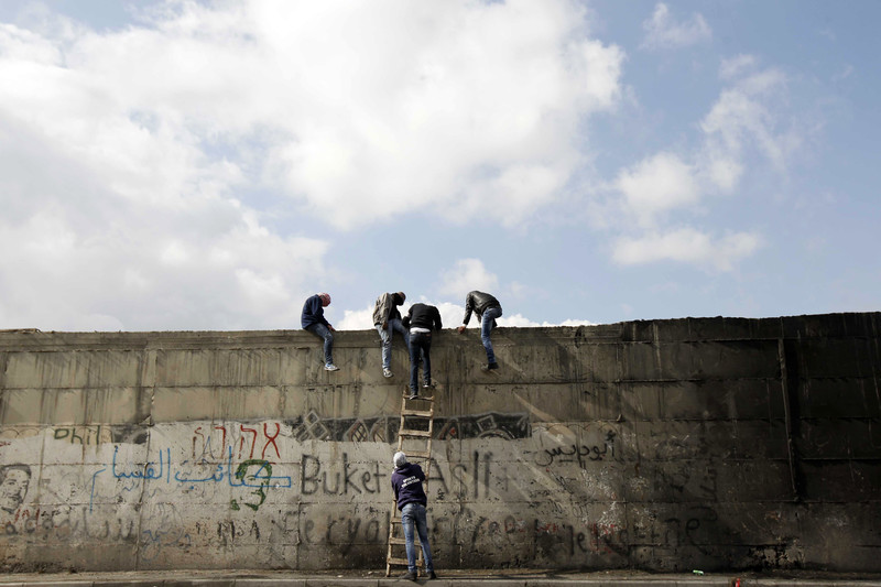 Palestinian protesters climb a ladder at Israel's controversial barrier that separates the West Bank town of Abu Dis from Jerusalem