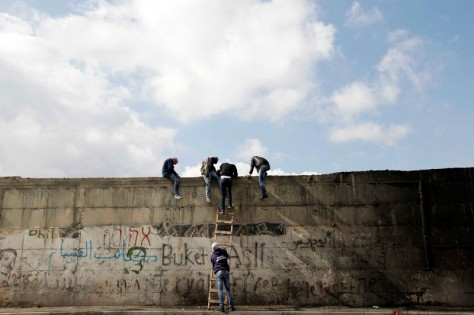 Palestinian protesters climb a ladder at Israel's controversial barrier that separates the West Bank town of Abu Dis from Jerusalem November 17, 2014. Photo by Muammar Awad