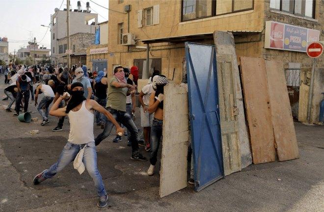 Palestinesi lanciano pietre contro la polizia israeliana durante gli scontri a Shuafat, un quartiere arabo di Gerusalemme, il 5 ottobre 2015. (Ammar Awad, Reuters/Contrasto)