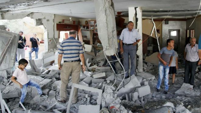 Palestinians inspect the home of the Abu Jamal family that was demolished by the Israeli armyAP