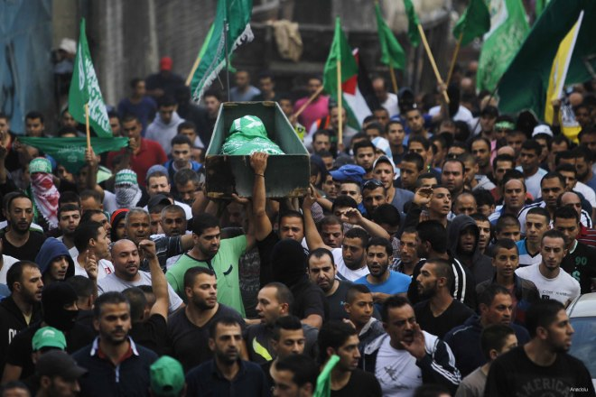 JERUSALEM - OCTOBER 10: Palestinians carry the body of Ahmad Salah who was shot dead by the Israeli army, during his funeral in Shuafat refugee camp in Jerusalem, on October 10, 2015. (Muammar Awad - Anadolu Agency)