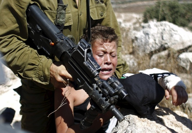 An Israeli soldier detains a Palestinian boy during a protest in the West Bank village of Nabi Saleh in August. (Mohamad Torokman/Reuters)