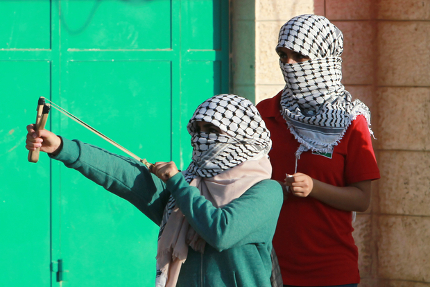 A Palestinian female protester uses a slingshot to throw stones towards Israeli security forces during clashes on October 15, 2015 in the West Bank city of Bethlehem. Israel has struggled to curb a spate of violence that has raised fears of a full-blown uprising, with more knife attacks shaking Jerusalem despite moves to set up checkpoints in Palestinian neighbourhoods and mobilise hundreds of soldiers. AFP PHOTO/ MUSA AL-SHAER