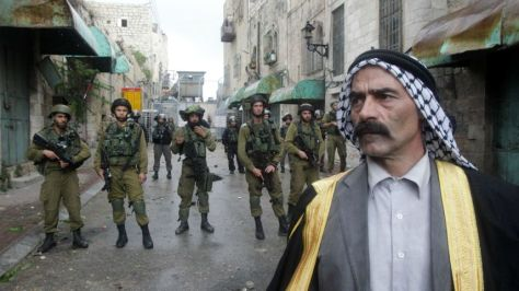 A Palestinian man stands in front of Israeli soldiers in Hebron, October 27, 2015.AFP